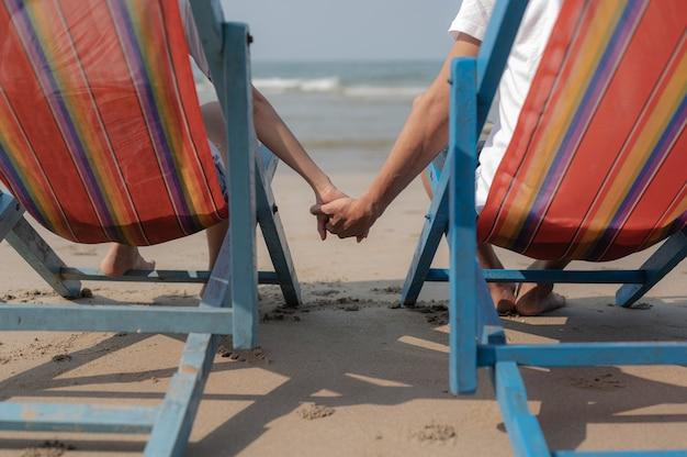 Una pareja sentada en una silla de playa y tomados de la mano en la playa.verano enamorado, concepto de día de san valentín.