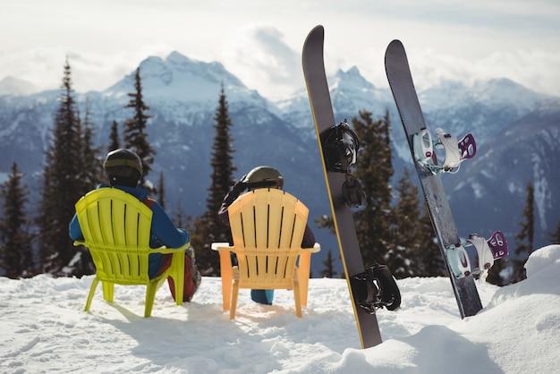 Pareja sentada en una silla por tablas de snowboard en la montaña cubierta de nieve