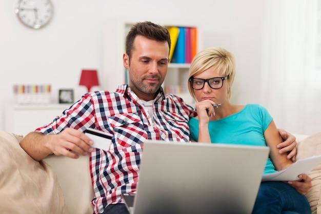 Pareja sentada en el sofá en casa y pagar la factura en línea