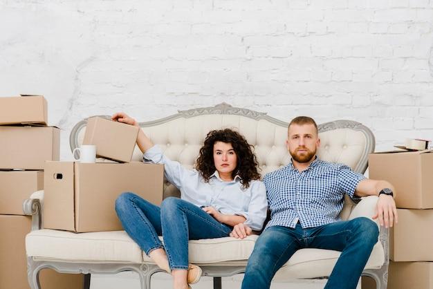 Pareja sentada en el sofá cerca de cajas de cartón