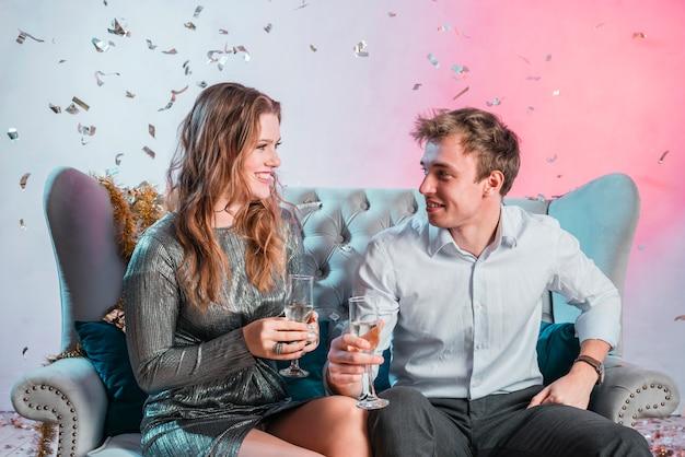 Pareja sentada en el sofá con copas de champán