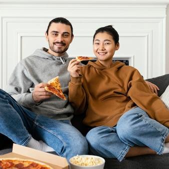 Pareja sentada en el sofá y pasar tiempo divertido juntos