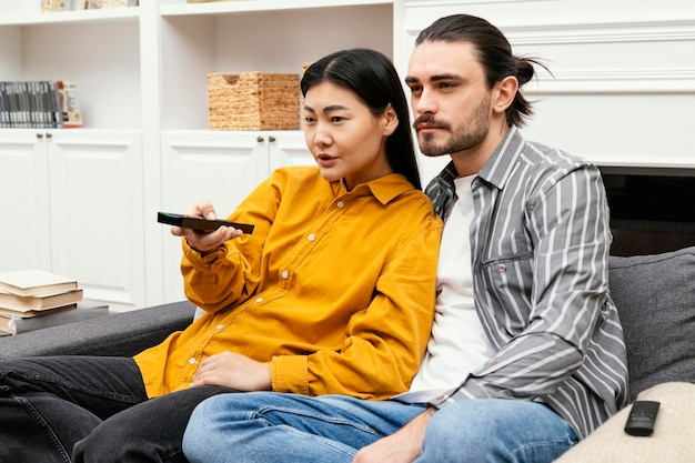 Pareja sentada en el sofá viendo la televisión y estar juntos