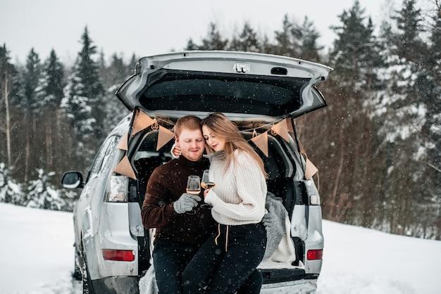 Una pareja sentada con tazas en la parte trasera de un coche y hacer un picnic en un bosque nevado
