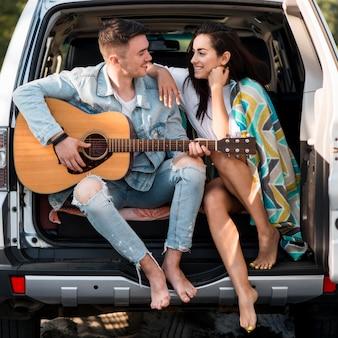 Pareja, sentado, en, baúl, con, guitarra
