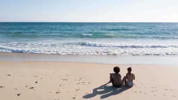 Pareja, sentado, en, playa arenosa