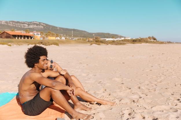 Pareja sentados juntos en la playa
