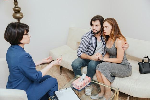 La pareja seria está sentada junta y abrazándose. están mirando al psicólogo. el doctor les está hablando y saludando con las manos.