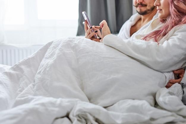 Pareja con smartphones en pijama en su cama, hombre y mujer caucásicos están buscando o navegando por internet