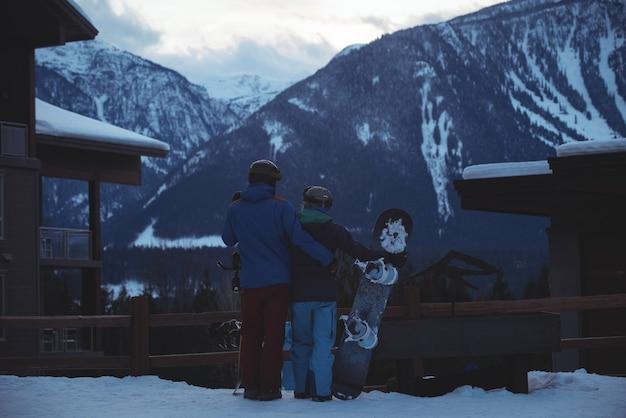 Pareja con snowboard de pie en campo cubierto de nieve