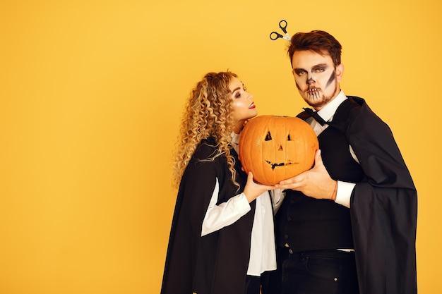 Pareja sobre un fondo amarillo. mujer vestida con traje negro. señora con maquillaje de halloween.
