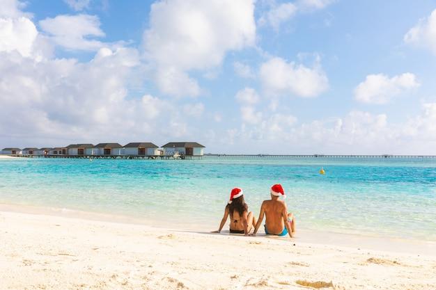 Pareja con sombrero de santa de navidad relajante en la playa