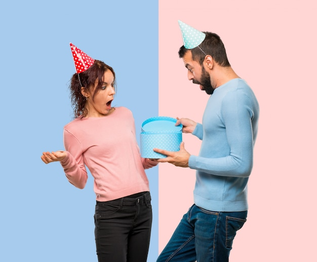 Pareja con sombreros de cumpleaños y sosteniendo un regalo sobre fondo rosa y azul