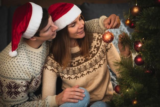 Pareja con sombreros de santa decorando el árbol de navidad