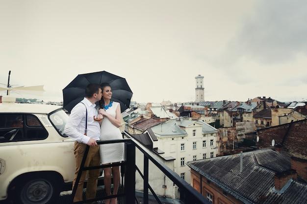 Pareja soñadora plantea bajo el paraguas en el techo