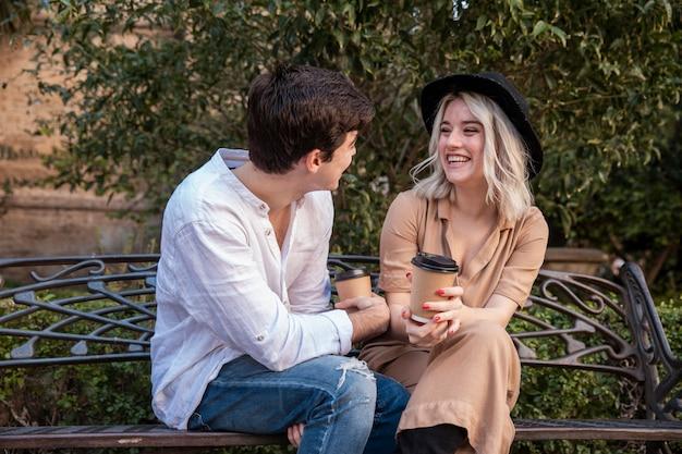 Pareja sonriendo y hablando en el banco en el parque
