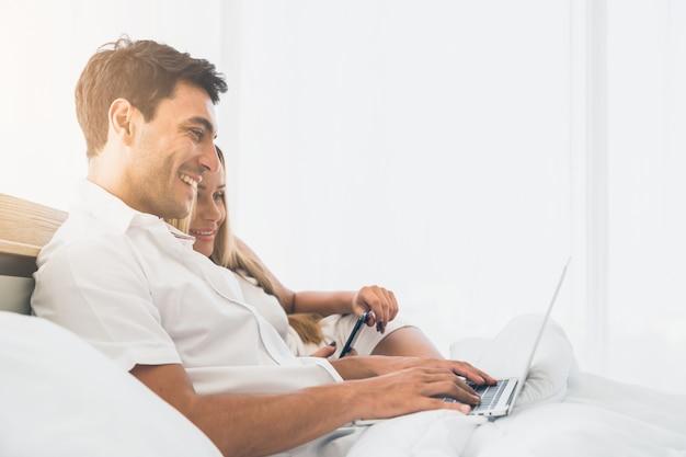 Pareja sonriendo muy feliz mientras usa la computadora portátil juntos en la cama temprano en la mañana