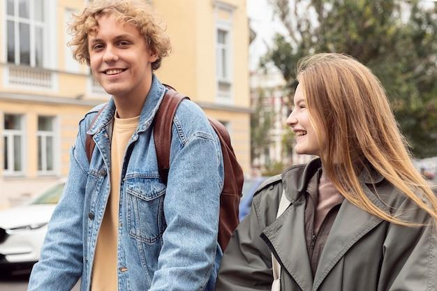 Pareja sonriente al aire libre en la ciudad en scooters eléctricos