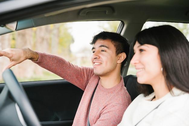 Pareja sonriente apuntando y mirando hacia adelante en el coche