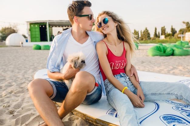 Pareja sonriente atractiva joven divirtiéndose en la playa jugando con perro