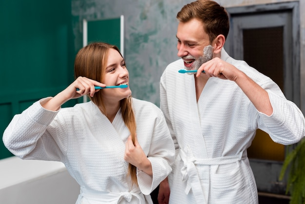 Pareja sonriente en batas de baño cepillarse los dientes