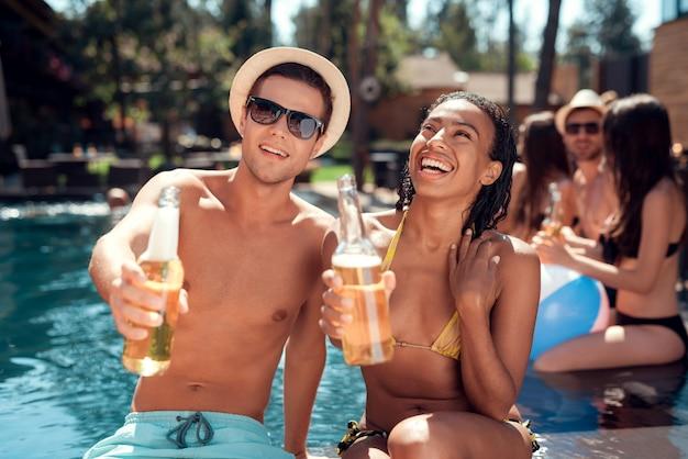 Pareja sonriente con bebidas alcohólicas en la piscina