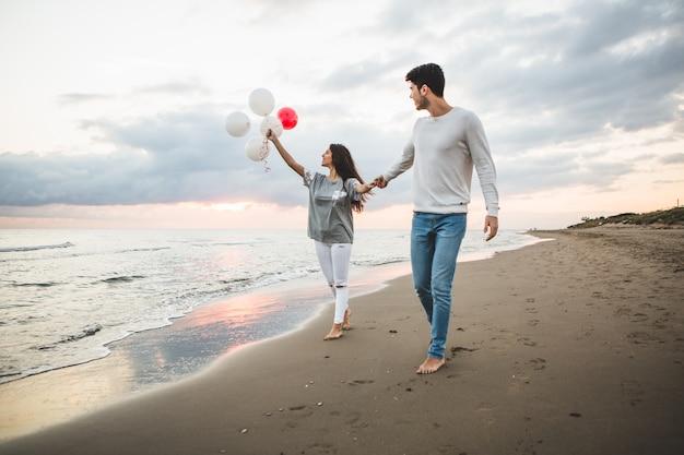 Pareja sonriente caminando por la playa con globos
