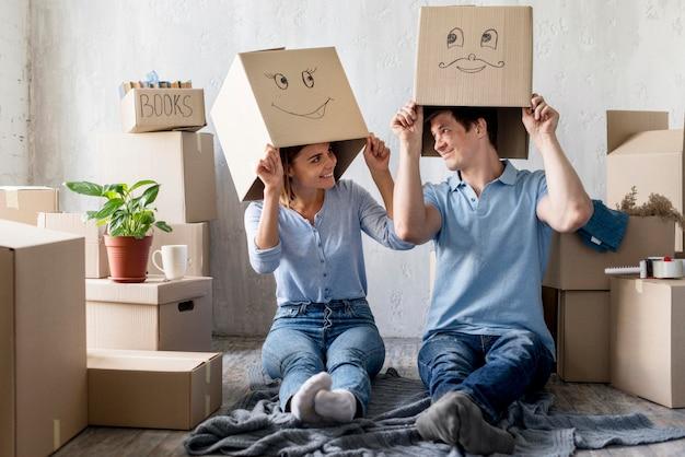 Pareja sonriente en casa el día de la mudanza con cajas sobre cabezas