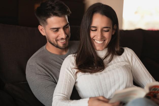 Pareja sonriente en casa leyendo tiempo
