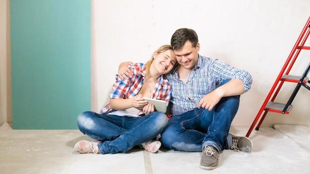Pareja sonriente en casa en proceso de renovación sentado en el suelo y sosteniendo la tableta digital.