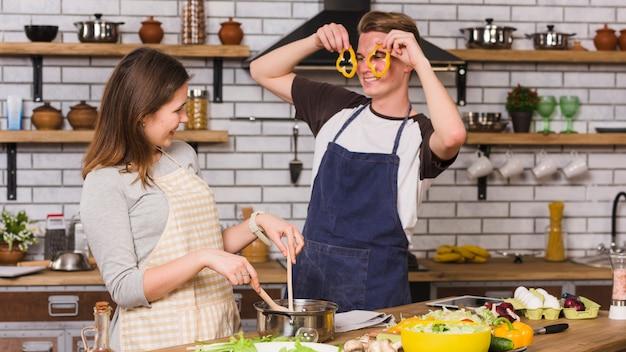 Pareja sonriente cocinando y jugando con verduras en la cocina