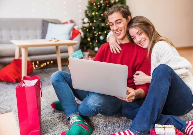 Pareja sonriente con la computadora portátil en el piso