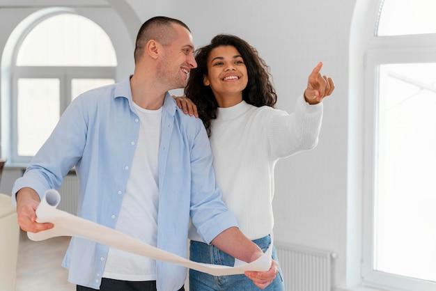 Pareja sonriente dentro de su nuevo hogar con planos de casas