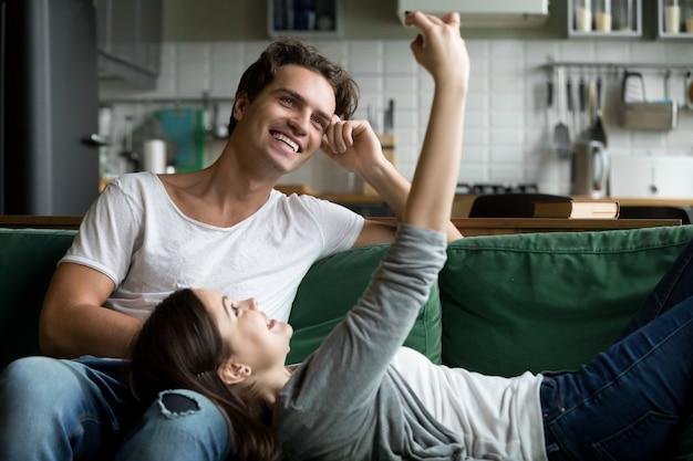 Pareja sonriente divirtiéndose con smartphone tomando selfie en casa