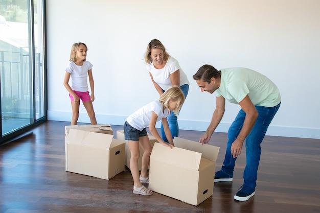 Pareja sonriente con dos hijas desembalaje de cajas en una habitación vacía