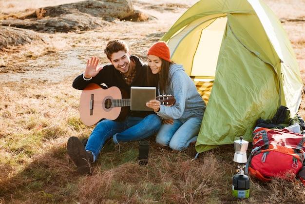 Pareja sonriente con guitarra cerca de la carpa con tableta