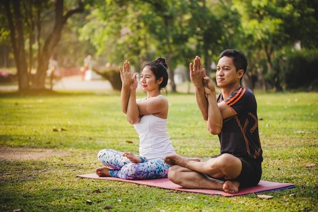 Pareja sonriente haciendo yoga en el parque