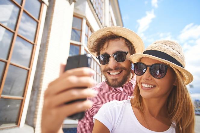 Pareja sonriente haciéndose un selfie primer plano