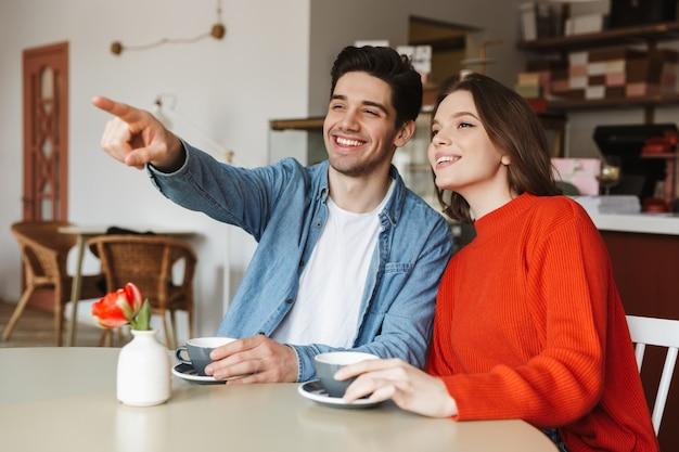 Pareja sonriente hombre y mujer sonriendo y señalando con el dedo a un lado, mientras bebe café en el restaurante