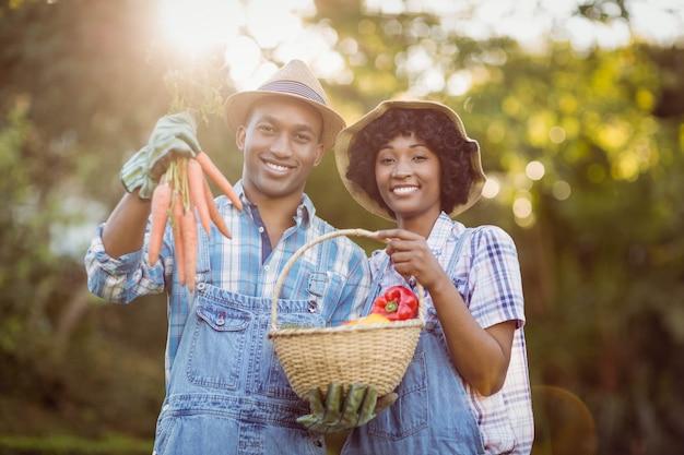 Pareja sonriente en el jardín con cesta y zanahorias