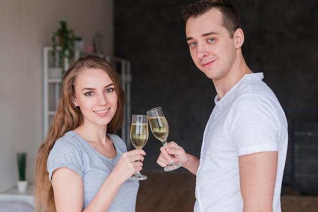 Pareja sonriente joven copas copas de bebida en casa