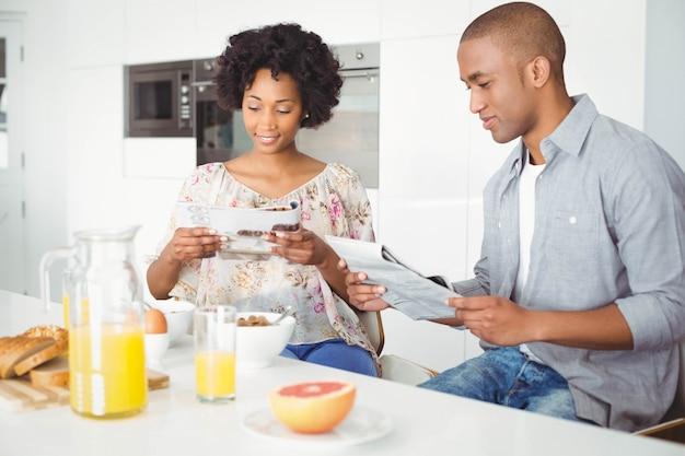 Pareja sonriente leyendo revistas y documentos durante el desayuno en la cocina