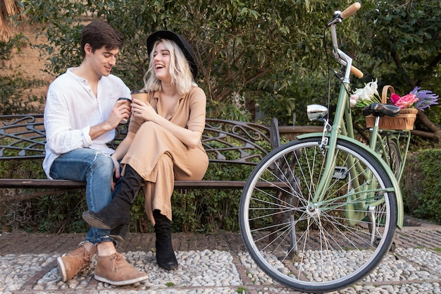 Pareja sonriente en el parque tomando café en el banco