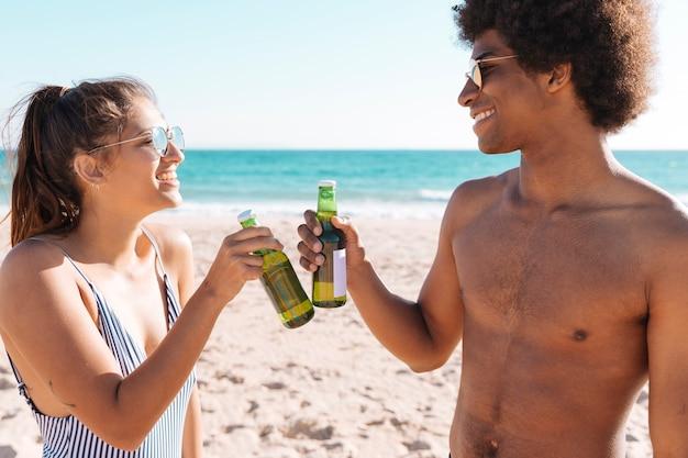 Pareja sonriente de pie en la orilla del mar y tintineo botella de bebida