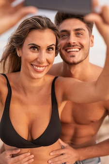 Pareja sonriente en la playa tomando selfie