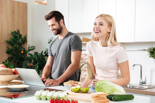 Pareja sonriente con portátil para cocinar en su cocina