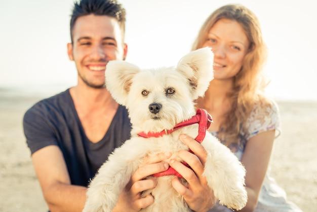 Pareja sonriente con retrato de perro en la playa