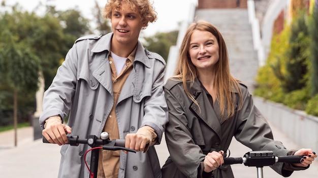Pareja sonriente con scooter eléctrico al aire libre