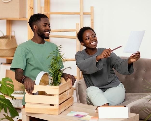 Pareja sonriente en el sofá haciendo un plan para redecorar la casa