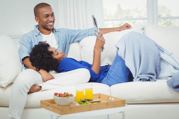 Pareja sonriente en el sofá leyendo el periódico juntos